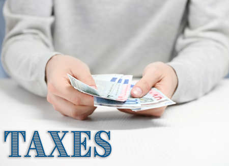 counting money: Man counting money above white table.Taxes concept Stock Photo
