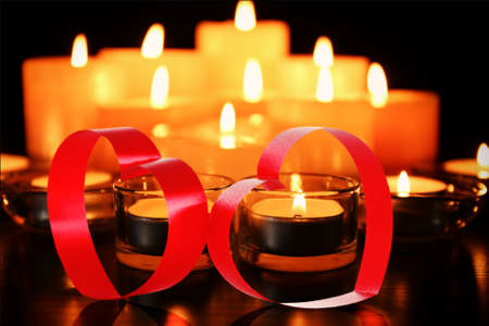 Ribbon shaped as heart on candles background