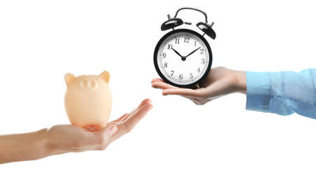 buying time: Time is money. Buying time. Hand with piggy bank and hand with alarm-clock, isolated on white