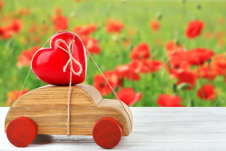 Wooden car with a red heart  tied to it on blurred field of poppies background