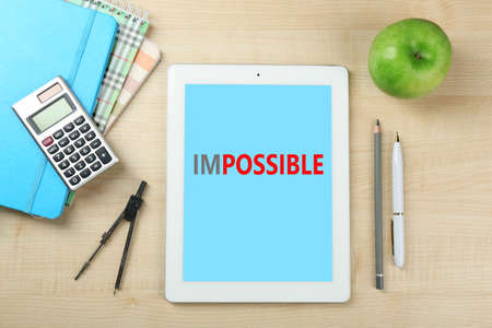 overcoming adversity: Word impossible transformed into possible on tablet-pc screen and office supplies
