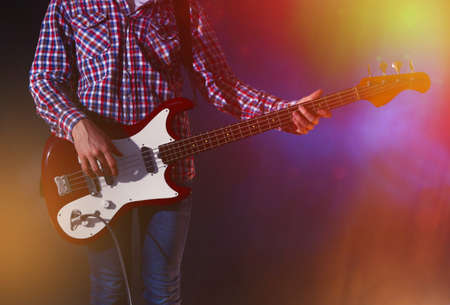 jamming: Young man playing electric guitar on lighted foggy background