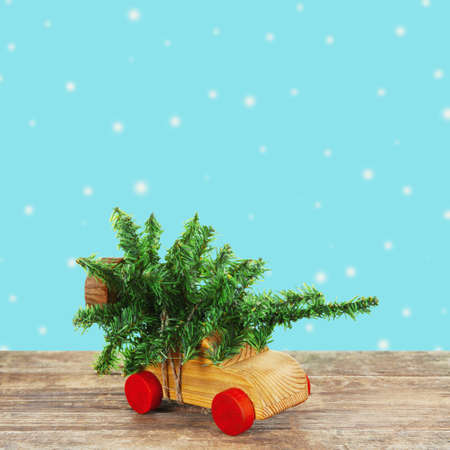 Wooden toy car carrying Christmas miniature  tree on color background Stock Photo