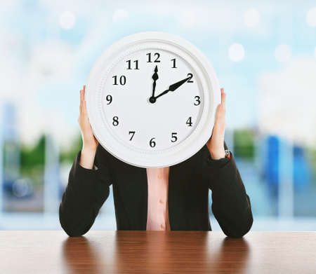 Woman holding big round clock on blurred background