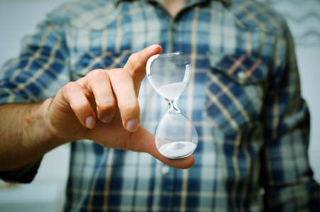Young man holding hourglass in hand on grey background Stock Photo