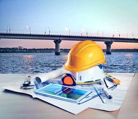 Table avec des dessins de construction et d'autres outils sur le fond du pont