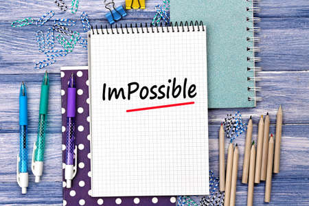 overcoming adversity: Word impossible transformed into possible on notebook page with school supplies