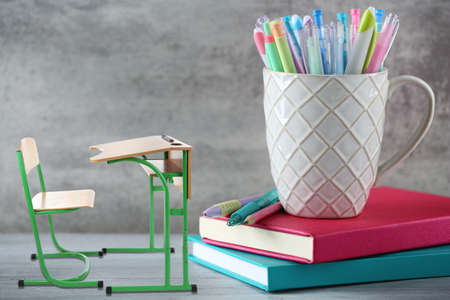 schooldesk: Wooden desk and chair with pens in ceramic cup on grey background