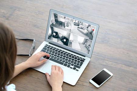 Frau, die Laptop am Tisch verwendet. Haussicherheitssystem-Konzept Standard-Bild - 66714317