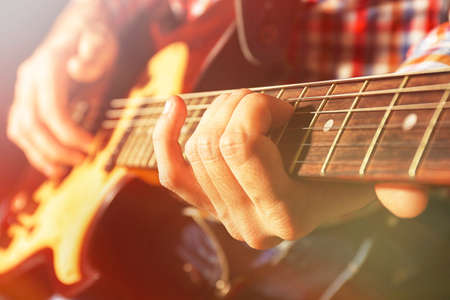 jamming: Young man playing on electric guitar on dark background with light effect Stock Photo