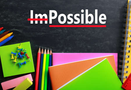 transformed: Word impossible transformed into possible on blackboard and school supplies
