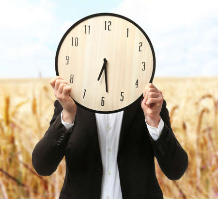 expires: Man in black suit covering his face with big clock on blurred field background