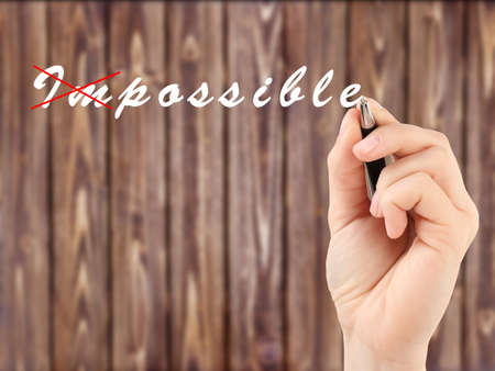 Human hand turning word impossible into possible Stock Photo