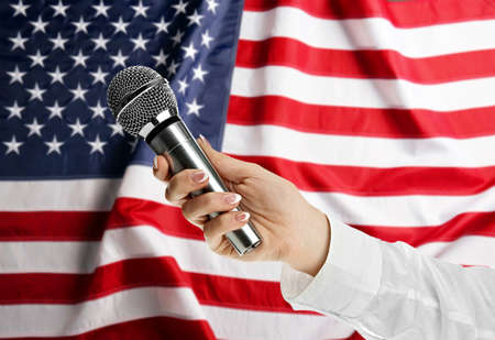 Female hand with microphone on USA National Flag background Stock Photo