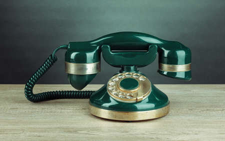 Retro phone on wooden table on grey background