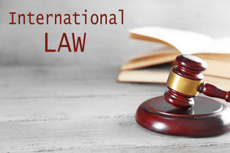 international law: Gavel and books on wooden table on grey background. International law concept