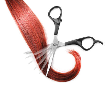Hairdressers scissors with strand of red hair, isolated on white Stock Photo