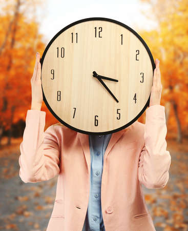 expires: Young attractive woman holds a clock on autumn background