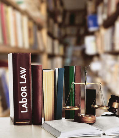 Wooden gavel with justice scales on table in library