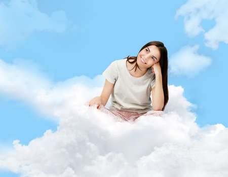 Young woman in pajamas sitting on blue cloudy sky