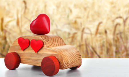 Wooden car with little red hearts on blurred field background