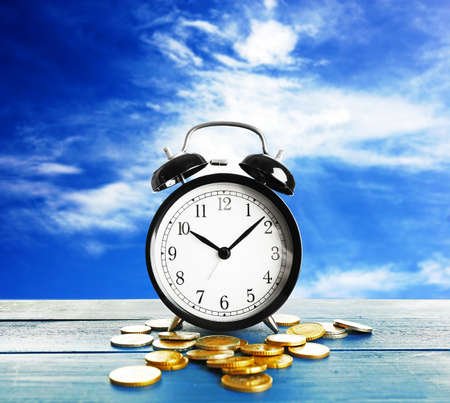 Alarm clock and money coins on sky background