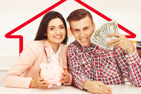salarios: Feliz pareja de jóvenes con billetes de dólares y hucha. Concepto de ahorro de dinero
