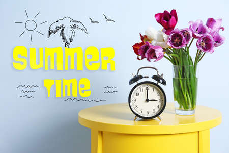 Alarm clock with tulips bouquet and text Summer time on light background