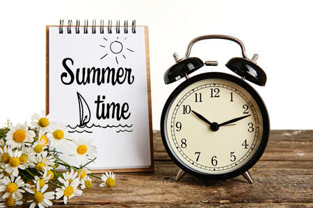 expires: Vintage clock, notebook with text Summer time and bouquet of daisy flowers on wooden table Stock Photo