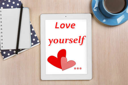 egoistic: Tablet with text Love yourself and cup of coffee on wooden table