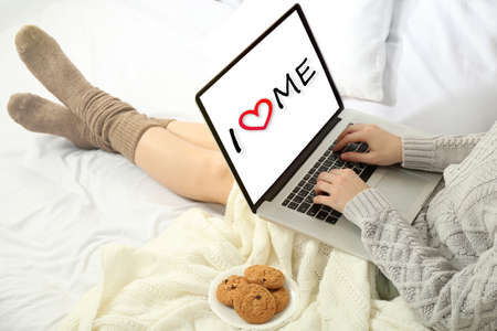 egoistic: Love yourself concept. Woman using laptop on her bed