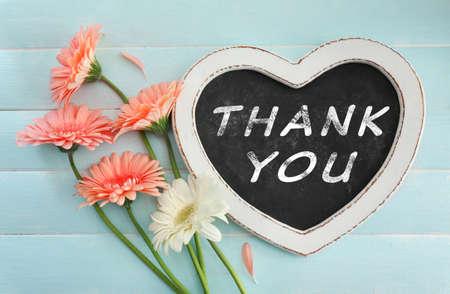 ガーベラと青い木製の背景に本文ありがとうの花束