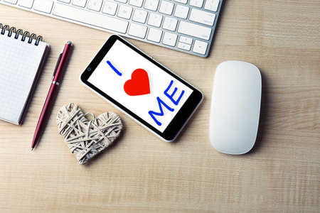 egoistic: Love yourself concept. Computer peripherals with white wicker heart, notebook and mobile phone on light wooden table Stock Photo