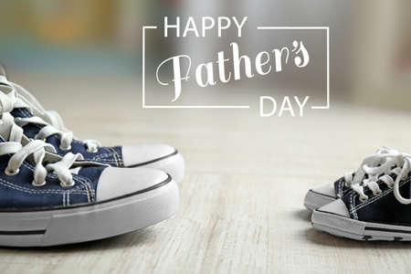 Happy fathers day concept. Big and small shoes on wooden floor