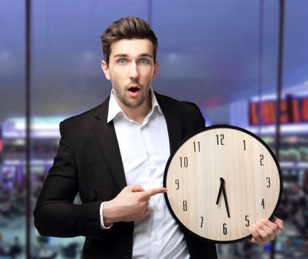 Man in black suit holding big clock on blurred urban background