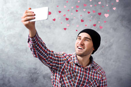 Young boy holding smart phone on grey wall background