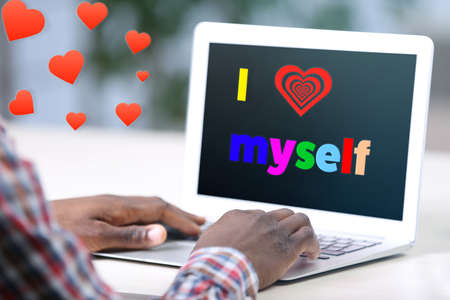 egoistic: Love yourself concept. Businessman with laptop in his office, text I Love Myself on screen