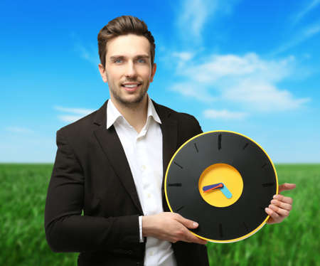 Man in black suit holding big clock on natural background