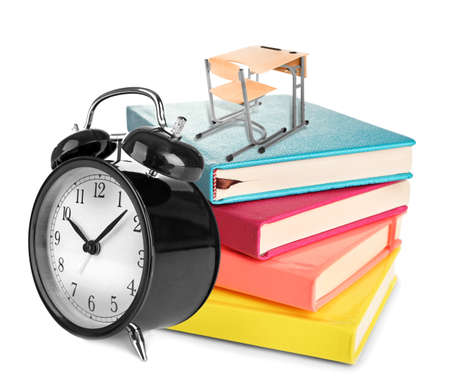 schooldesk: Little wooden desk and chair on colorful notebooks with alarm clock isolated on white Stock Photo