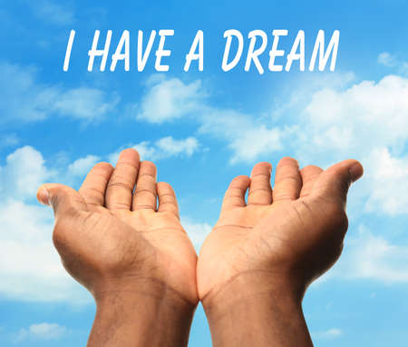 Martin Luther King Day. Male hands with text I Have a Dream on blue sky background