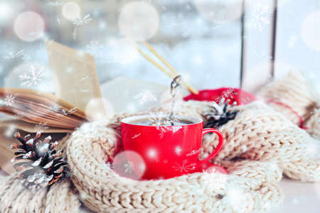 Cup of hot drink in on the windowsill in living room. Comfortable winter weekend or holidays at home. Snow effect