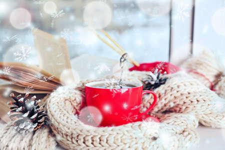 Tasse de boisson chaude sur le rebord de la fenêtre du salon. Week-end d'hiver confortable ou vacances à la maison. Effet de neige