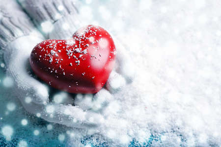 Hands in warm white gloves holding red heart on snowy background. Snow effect Stock Photo