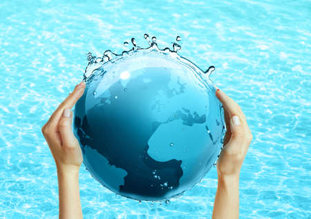 hands holding globe: Female hands holding globe on blue water background Stock Photo