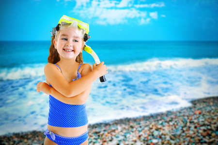 devise: Happy little girl in blue swimsuit with diving mask on blurred sea background