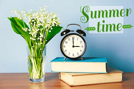 Alarm clock with lily bouquet and text Summer time on blue background