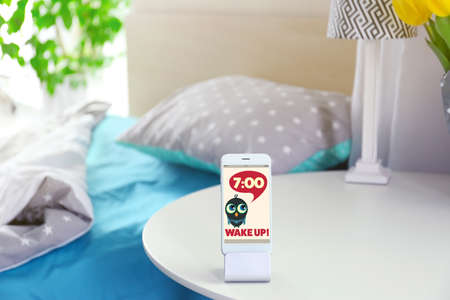 Smart phone with stand on a bedside table in a room Stock Photo