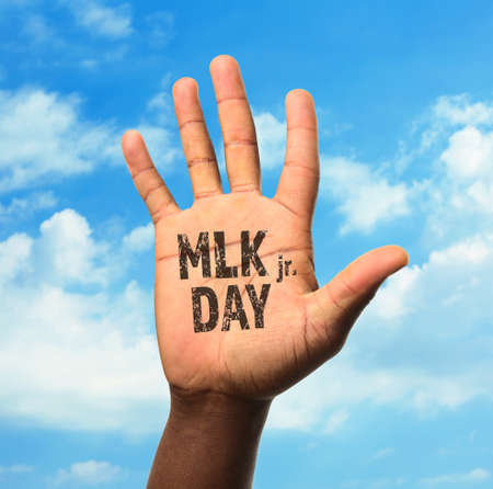 Martin Luther King Day. Male hand on blue sky background