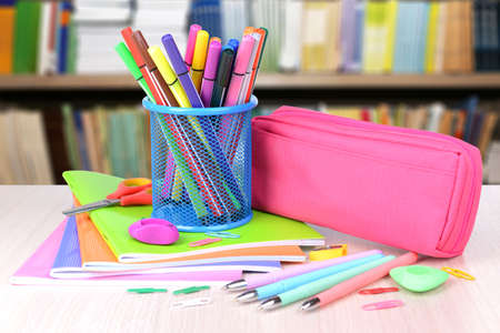 Bright school supplies on blurred library background