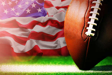 American football on green grass, on flag of United States of America background Stockfoto